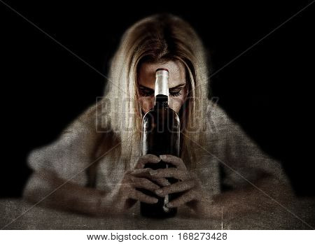 drunk blond woman alone in wasted depressed expression looking thoughtful with white wine glass on grunge dirty background in alcohol abuse and alcoholic housewife concept