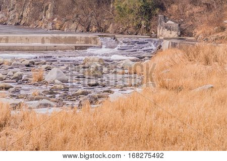 Small river running over a man made waterfall that is use to aerate the river