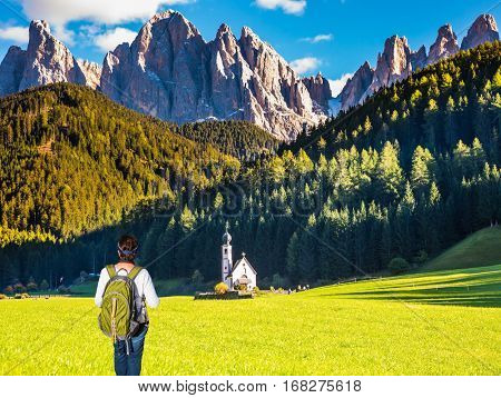Elderly active woman-tourist with backpack raptured church. The concept of an active and eco-tourism. Sunny day in Dolomites, Tirol. Forested mountains surrounded by green Alpine meadows