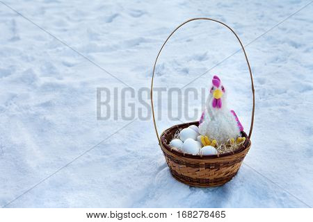 Basket with paraphernalia on Easter rooster and Easter eggs lying in basket in the snow.