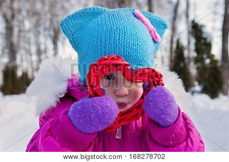 Little girl holding in their hands hearts themes Valentine's day the day of the winter on the street in the Park.