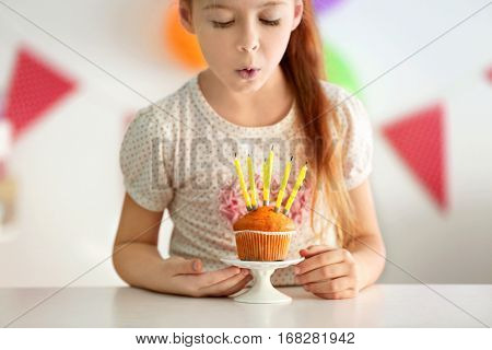 Cute little girl blowing out candles on birthday cake, close up view