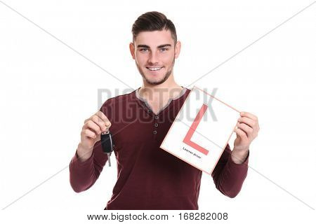 Young man with learner driver sign and car key on white background