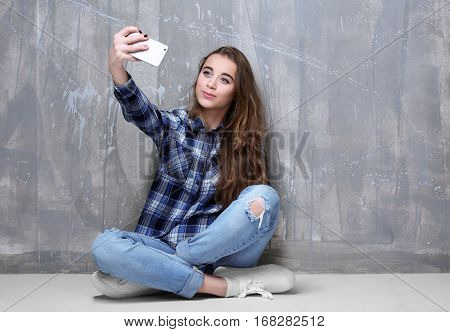 Pretty teenager girl taking photo on color background