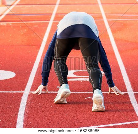 A sprinter training for the 100 mete dash on a high school track in the winter