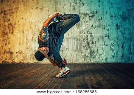 Young man break dancing and standing on one leg on wall background. Vibrant colors effect. Tattoo on body.