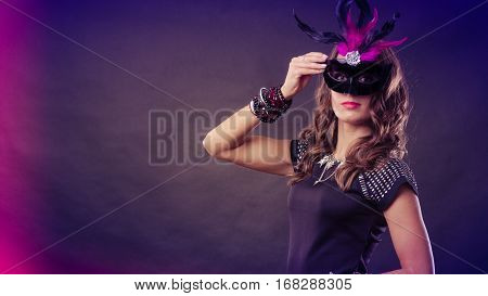 Holidays people and celebration concept. Woman with carnival venetian mask on dark background.