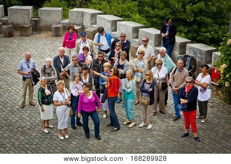 LISBON PORTUGAL - JUNE 11 2013: Group of tourists listening to the guide and looking to the building of Palace of Sintra located in the town of Sintra in Lisbon