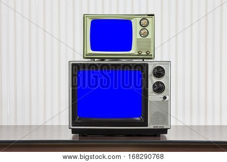 Two vintage televisions stacked on table with chroma key blue screens.