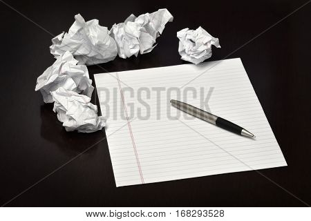 Pen and paper on a desk with discarded trashed ideas written ouit