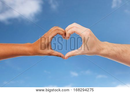 love, charity, valentines day and international concept - close up of man and woman hands making heart symbol over blue sky and clouds background