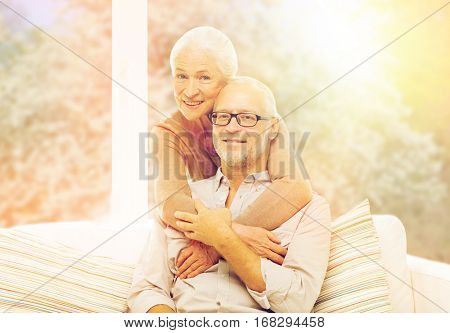 family, relations, age and people concept - happy senior couple hugging on sofa