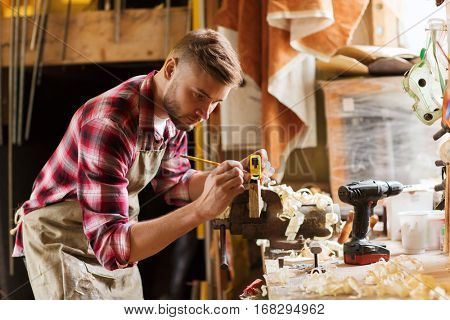 profession, carpentry, woodwork and people concept - carpenter with ruler measuring wood plank at workshop poster