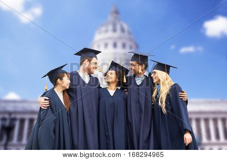 education, graduation and people concept - group of happy international students in mortar boards and bachelor gowns over american white house background