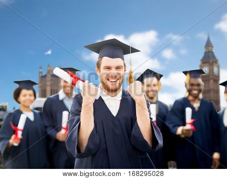 education, gesture and people concept - group of happy international students in mortar boards and bachelor gowns with diplomas celebrating successful graduation over london city background
