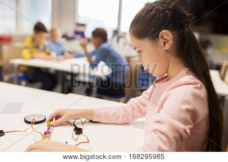 education, children, technology, science and people concept - happy girl building robot at robotics school lesson