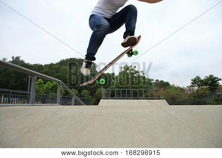 skateboarder legs doing a ollie trick at skatepark