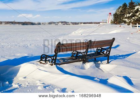 Parch bench under the snow along the waterfront of Charlottetown, Prince Edward Island, Canada.