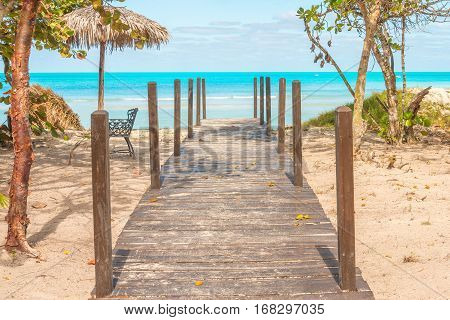 Boardwalk leading to beautiful blue waters of the sea.