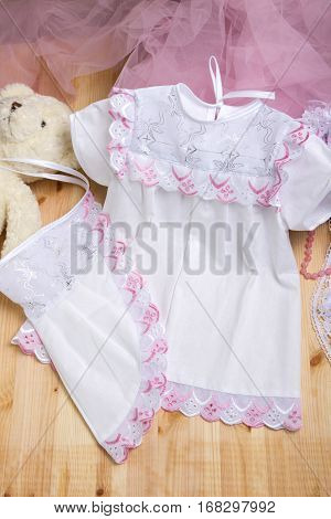 Christening dress. Set of christening clothes on wooden background