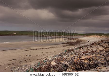 Orkneys Scotland - June 5 2012: The beach at Skara Brae Neolithic Settlement under heavy dark stormy sky. Sand rocks and rubble. Quiet ocean and a green band of meadows with white farms on the horizon.