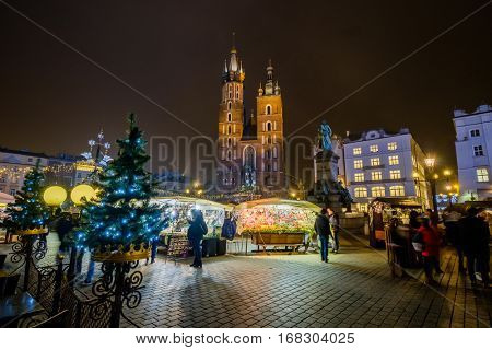 Krakow, Poland - December 19, 2016: People visit Christmas market at main square in old city of Krakow, Poland
