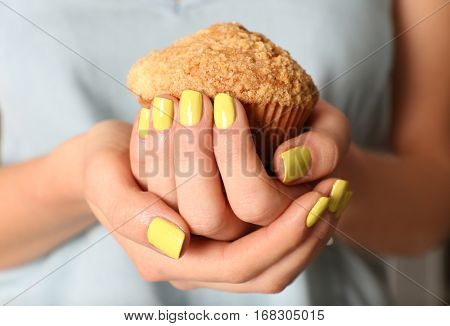 Female hands with beautiful nail art holding muffin, closeup