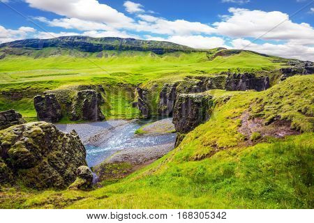 The concept of active northern tourism. The striking canyon in Iceland. Bizarre shape of cliffs surround the stream with glacial water. Green Tundra in summer
