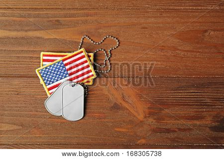 Military ID tags with USA flag on wooden background