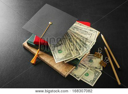 School supplies, graduation hat and dollar banknotes on blackboard. Pocket money concept
