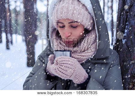 Close-up of pretty female blowing on tea while enjoying a mug of tea. Winter fashion. Portrait of a beautiful woman in warm clothes outdoor nearby the tree