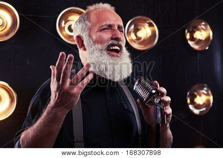 Studio portrait of shrewd look of emotional gray bearded man singing in a silver vintage microphone isolated over spotlights. Passionate look into the camera over spotlights