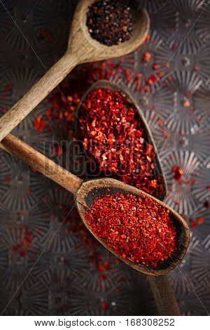 red hot chillies pepper flakes in vintage wooden spoons on textured metal background