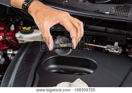 closeup engine oil cap in hand, transportation concept