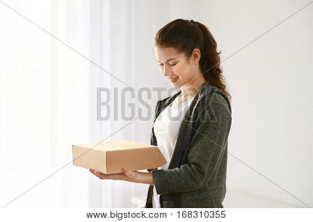 Beautiful young woman with parcel at home