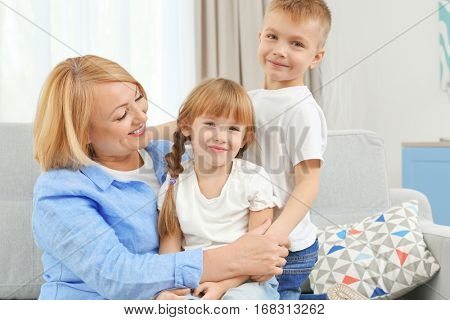 Happy grandmother with grandchildren on couch
