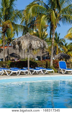Pool with sun chairs and palm trees in an all inclusive hotel. Cayo Largo