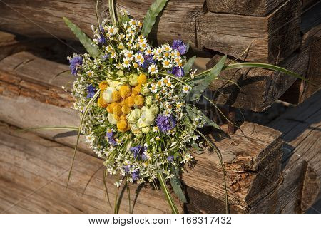 Colorful posy near wood. Brunch made of dasies