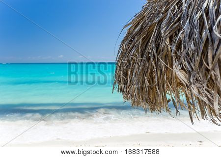 Beach Umbrella made of palm leafs on the background of an exotic beach in Cayo Largo