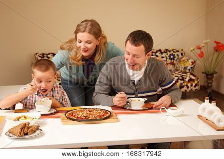 Happy family by the table with pizza eating together
