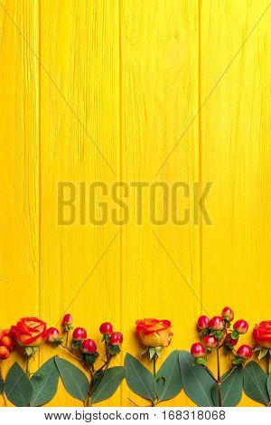 Hypericum, roses and rowan on yellow wooden background