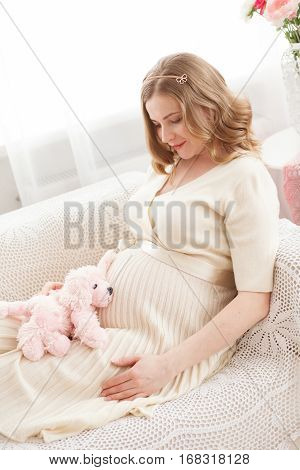 Pregnant blond woman sits on the couch at home. Modern interiori pastel colors. Professional style and make-up