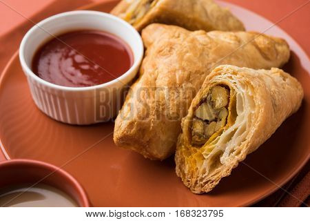 stuffed vegetable or veg puff or puf or samosa, famous indian snack menu, served with hot tea, selective focus