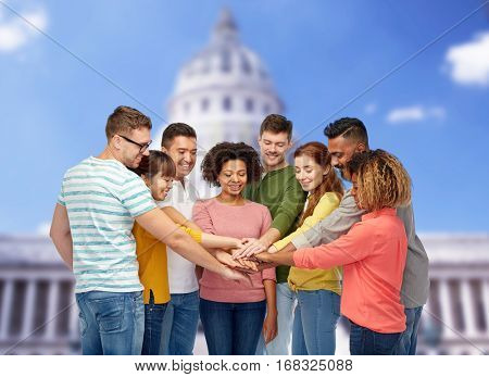 diversity, teamwork, race, ethnicity and people concept - international group of happy smiling men and women holding hands together over united states capitol background