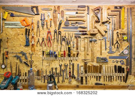 carpentry, woodwork and equipment concept - work tools hanging on wall at workshop
