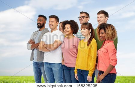 diversity, race, ethnicity and people concept - international group of happy smiling men and women over blue sky and grass background