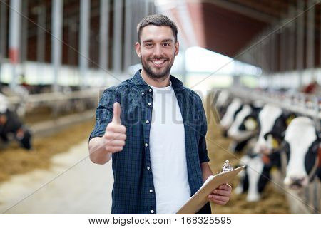 agriculture industry, farming, people and animal husbandry concept - happy smiling young man or farmer with clipboard and cows in cowshed on dairy farm showing thumbs up hand sign