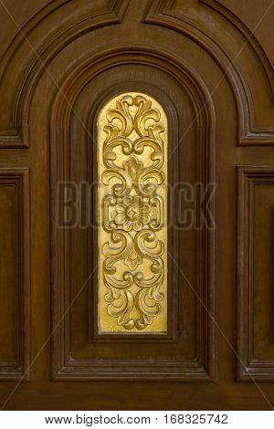 old teak wood door with gold carving.