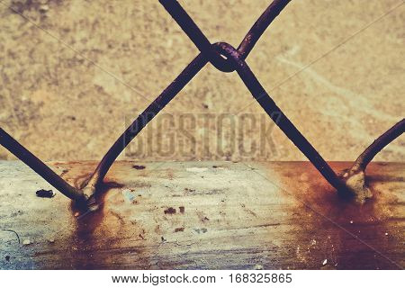 Close up of rusty steel wire mesh fence vintage tone