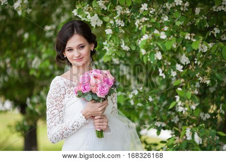 Young beautiful woman bride with pink wedding bouquet in blooming garden
